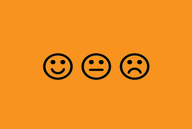 a smiley, a neutral face and a sad face in black on orange background