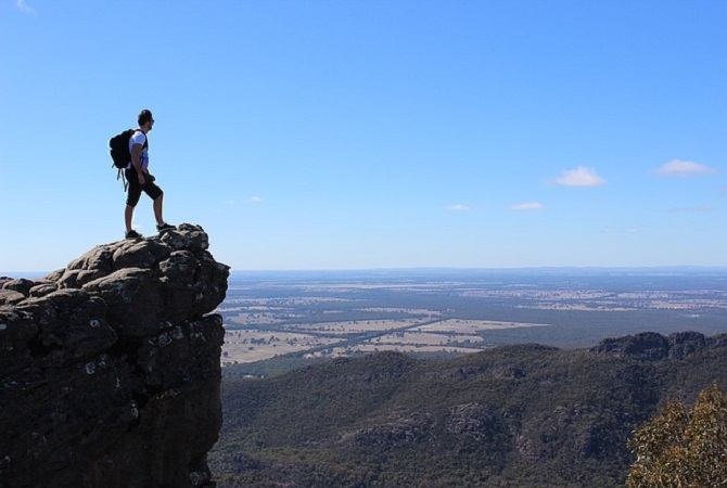 man stands at top of cliff