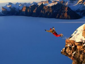 base jumper leaping from a rocky mountain