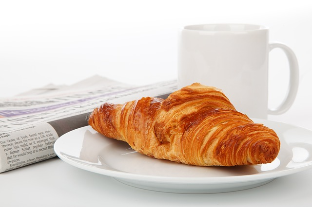 croissant, newspaper and mug