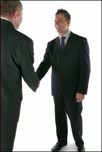 Two business men in suits shaking hands and smiling