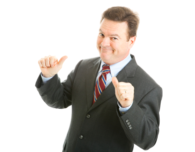 Man in business suit pointing to self