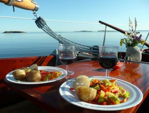 Nice meal for two with wine on deck of yacht overlooking the water