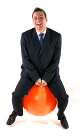 laughing business man in suit on spacehopper